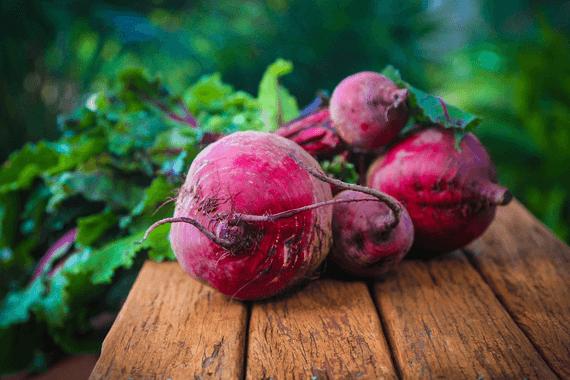 5 ripe beets on cutting board.