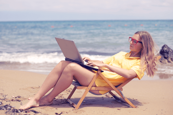 Digital Nomad working from Caribbean beach, computer on lap.