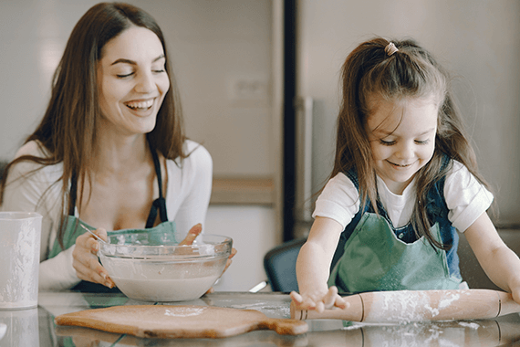 Mother and daughter in kitchen baking vegan cookies.