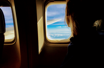 Woman staring out jet plane window