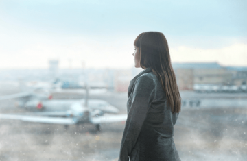 Woman with travel anxiety staring at airplane.