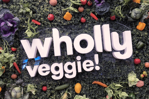 "6 foot sign reading ""Wholly Veggie!"" at entrance to Montreal Vegan Festival"