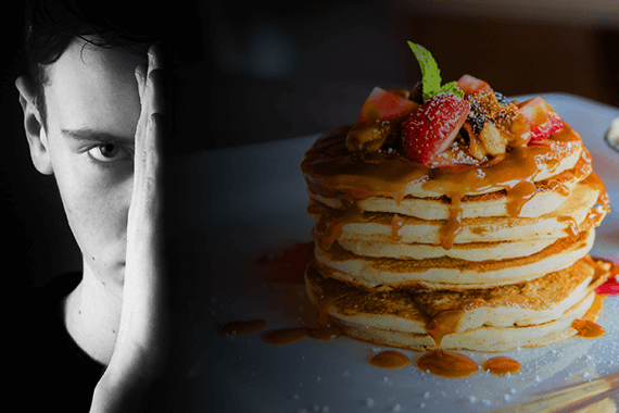 Man reviews food intolerance test while scowling at pancakes.