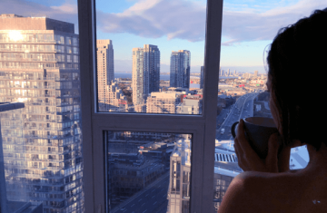 Woman drinking tea and looking at Toronto skyline from condo window.